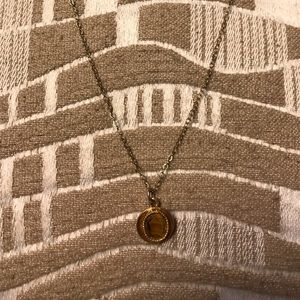 Gold necklace and gold pendant with brown rock